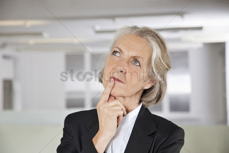 Office worker : Thoughtful senior businesswoman looking up in office