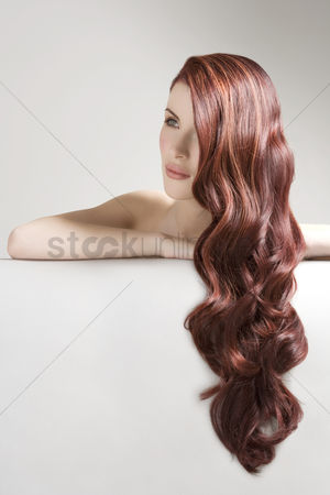 Young woman : Thoughtful woman with long red dyed hair against gray background