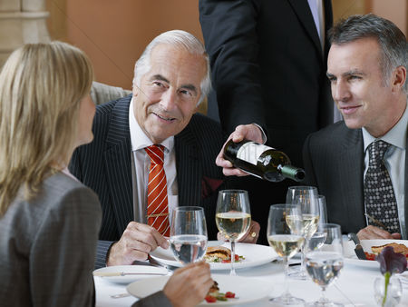 Wine bottle : Three business people talking at restaurant table waiter serving wine