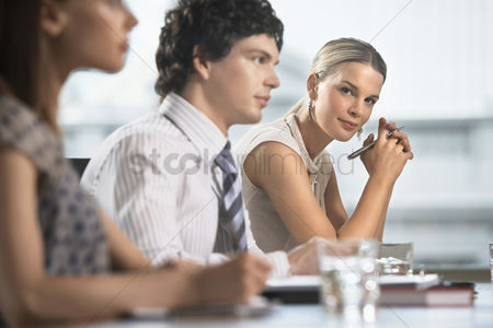 Interior : Three businesspeople sitting at business meeting