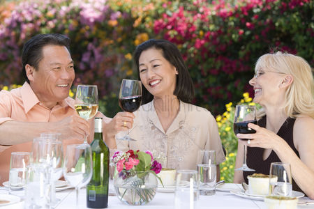 Wine bottle : Three friends toasting at outdoor table