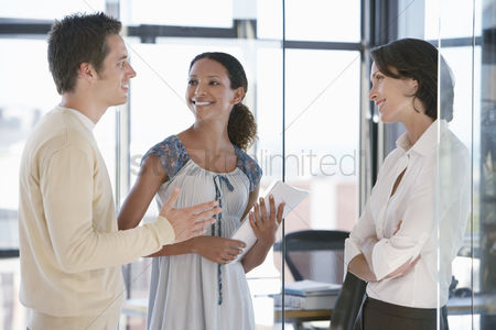 Relationships : Three office workers standing in office talking