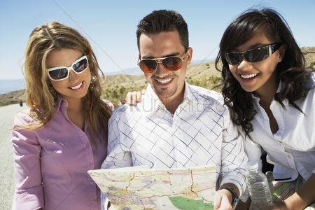 On the road : Three people looking at map on side of desert road