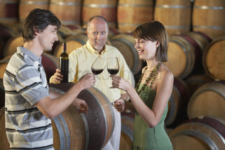 Toasting : Three people wine-tasting beside wine casks