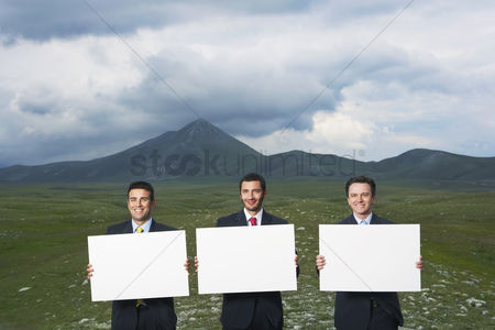 Moody : Three smiling businessmen standing in mountain field holding blank signs front view