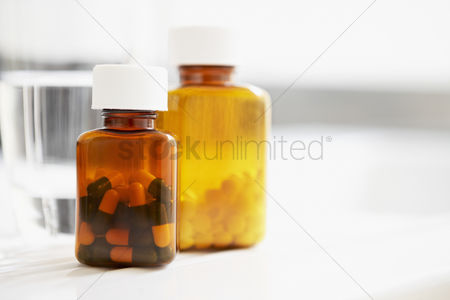Medication : Two bottles of pills and glass of water on table close up