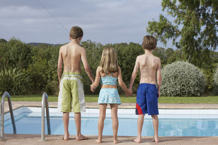 Diving : Two boys and girl  6-11  standing on edge of pool back view