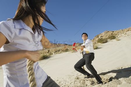 Rope : Two business people playing tug of war in the desert