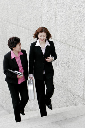 Stairs : Two business women chatting while walking up the stairs