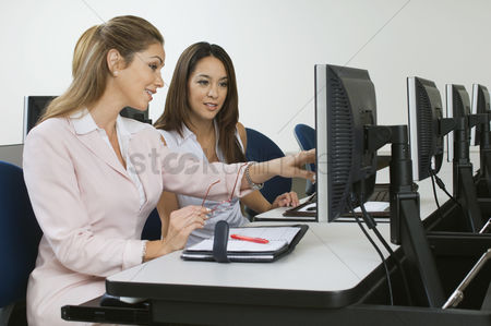 Assistance : Two business women sitting in computer classroom