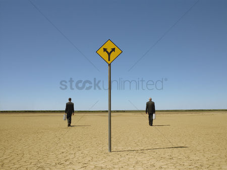 Two people : Two businessmen with briefcases in desert back view road sign in foreground