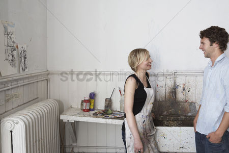 Pocket : Two college students chatting by sink in art studio