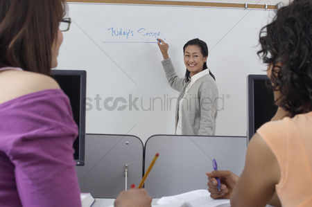 Teacher : Two female students watching teacher in computer classroom