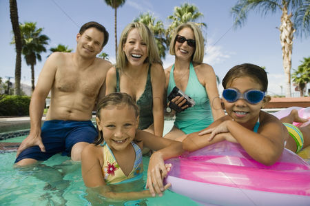 Posed : Two girls  7-9  with parents and grandmother in swimming pool portrait