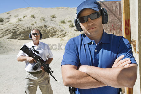 Firing : Two men at firing range in desert portrait