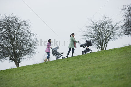 Pushing : Two mothers pushing stroller uphill