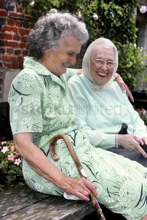 Outdoor : Two old women having fun sitting on the bench talking
