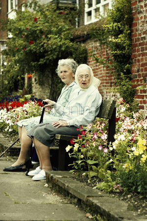 Bespectacled : Two old women sitting on the bench together