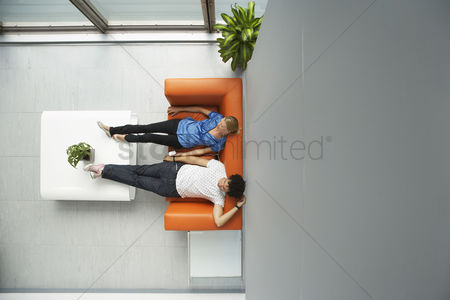 Two people : Two people reclining on couch in reception room view from above