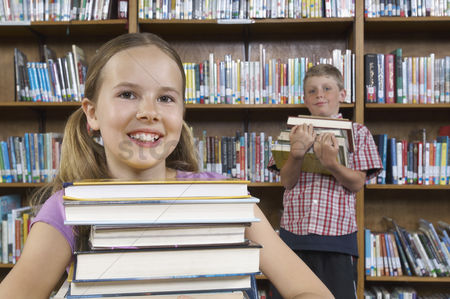 Pupil : Two school children with books in library portrait