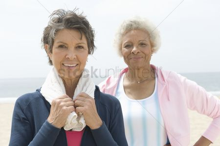 Fitness : Two senior women stand on coastal promenade