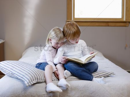 Denim : Two sisters sit reading on a single bed