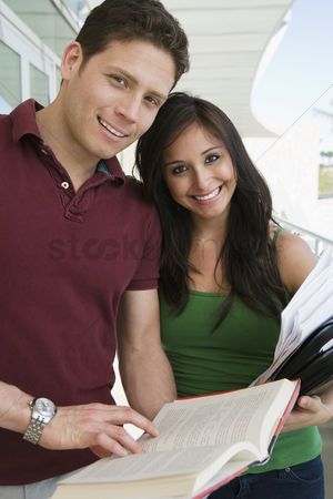 Pupil : Two students holding books at school smiling portrait