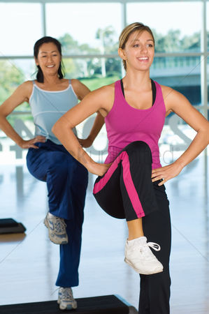 Fitness : Two women in step aerobics class