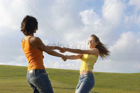 Dancing : Two young swinging each other around in mountain field side view