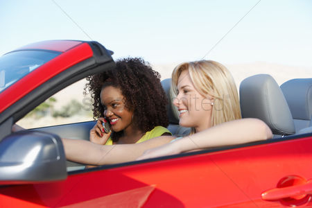 Curly hair : Two young women driving red convertible