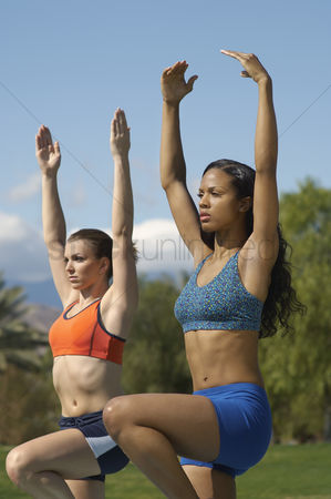 Arm raised : Two young women exercising in park