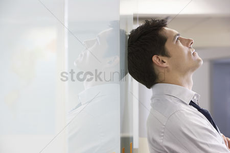 Interior : Unhappy businessman leaning back against office wall and looking at ceiling side view