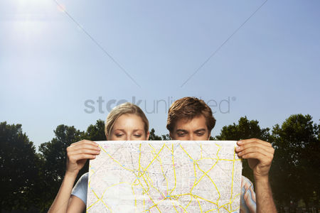 England : Vacationing couple in park looking at large map
