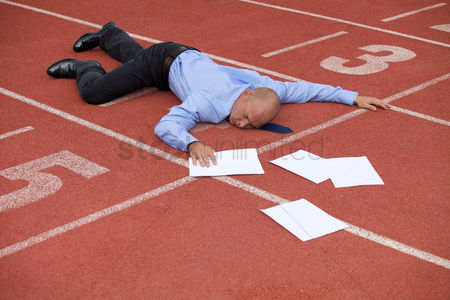 Sports : View of a businessman lying on a race track