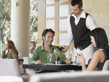 Wine bottle : Waiter pouring wine for couple at outdoor restaurant
