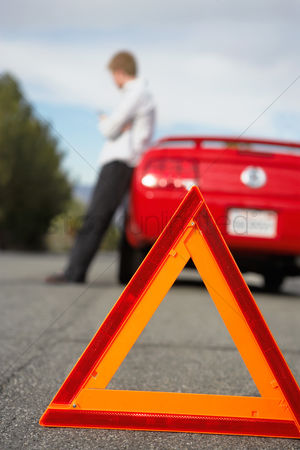 On the road : Warning triangle standing by man leaning on broken down car