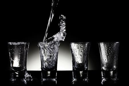 Refreshment : Water pouring into shot glasses