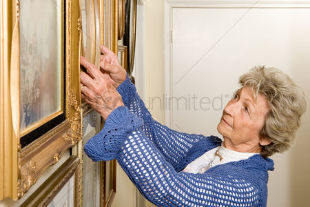 Housewife : Woman adjusting picture frames