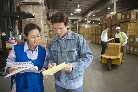 Notepad : Woman and man talking in distribution warehouse