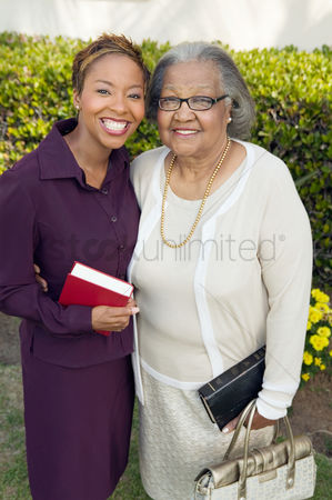 Religion : Woman and mother standing in garden with bibles portrait