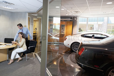 Show : Woman and salesman sitting in car showroom office