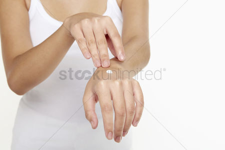 Femininity : Woman applying lotion on her hand