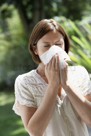 Blowing : Woman blowing nose in garden