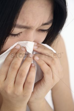 Blowing : Woman blowing nose with tissue