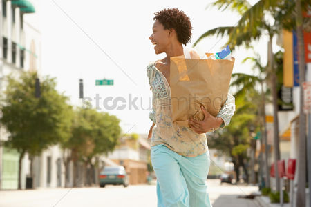 Curly hair : Woman carrying grocery bag while walking profile
