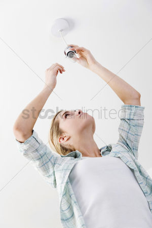 Careful : Woman changing the light bulb
