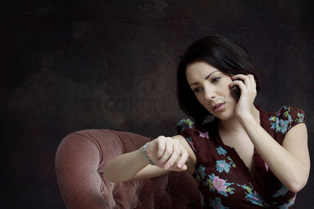 Cell phone : Woman checking her watch while talking on the phone