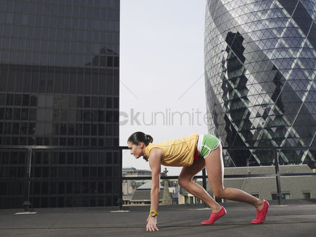 England : Woman crouching in starting position on downtown rooftop side view london england