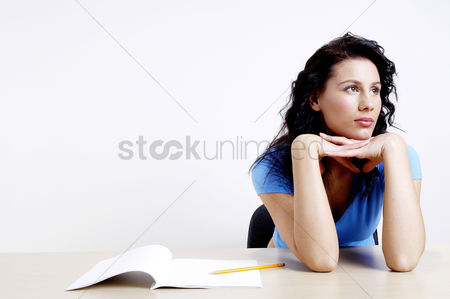 Thought : Woman daydreaming with pen and pencil on the table
