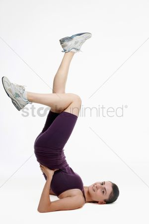 Practising yoga : Woman doing shoulder stand